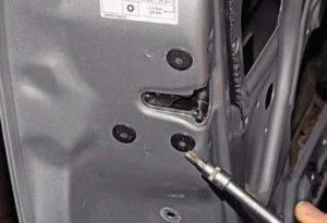 Ключом отворачиваем три винта крепления замка к торцу двери