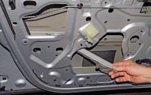 Выводим направляющую через технологическое отверстие во внутренней панели двери и снимаем её